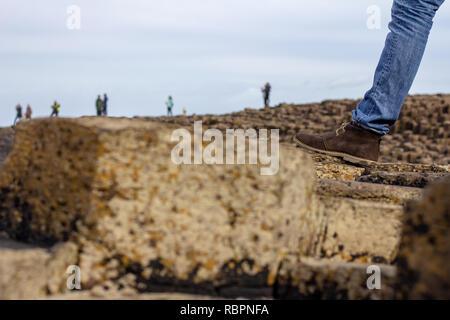 Jean bleu jambe vêtue et brown bottes d'pied du randonneur sur les roches, les personnes non identifiables dans la distance Banque D'Images