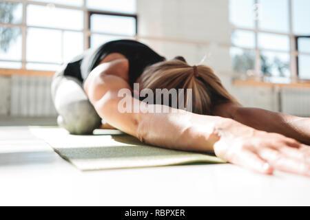 Athletickwoman les jeunes faisant du yoga l'exercice sur tapis de fitness gym soleil blanc en début de morling. Fille sportive repose après un entraînement de stress Banque D'Images