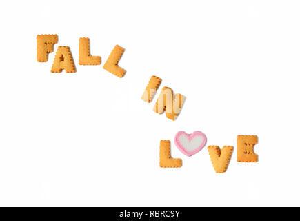 Le mot tomber en amour écrit avec des biscuits en forme d'alphabet en forme de coeur et d'un bonbon guimauve sur fond blanc, la Saint-Valentin Banque D'Images