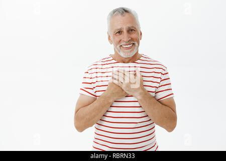 Taille plan sur charmingkind et heureux grand-père heureux fils touché de voir grandir bon homme tenant la main appuyée sur la poitrine en reconnaissant à la joyeuse smiling geste réconfortant à huis clos Banque D'Images