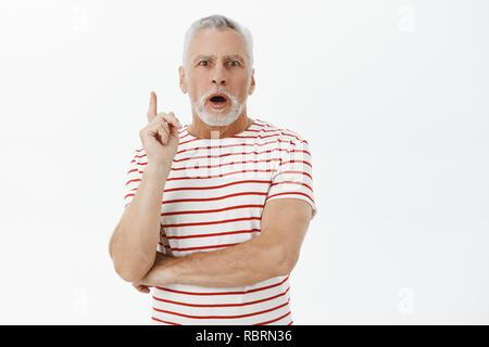 Taille plan sur concernés bien réfléchie et déterminée hauts père avec des cheveux blancs et sa barbe en t-shirt à rayures de parler l'ajout des suggestiong index comme si avoir une idée ou un plan au mur gris Banque D'Images