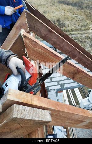 Couper les travailleurs les chevrons sur le toit de la tronçonneuse house Banque D'Images