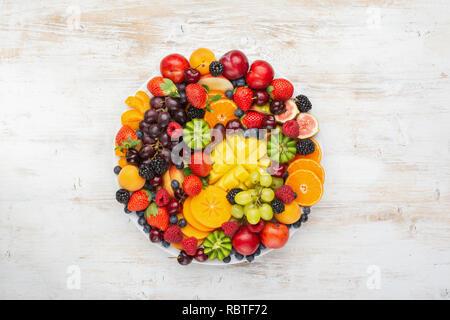 Plateau de fruits sains, Fraises Framboises Oranges Pommes Prunes Raisins kiwis mangues bleuets sur le plaqueminier de table en bois blanc Banque D'Images