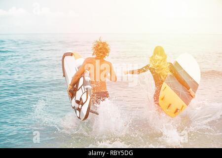 Les surfeurs à la plage- Smiling couple de surfers marche sur la plage et s'amuser en été. Sport extrême et vacances