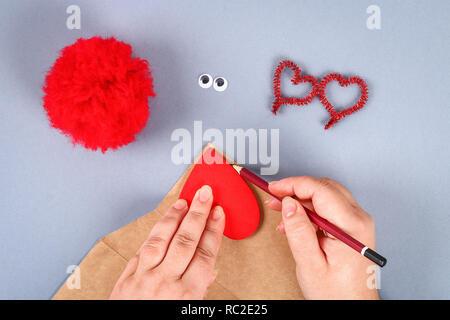 Bricolage artisanal rouge monster pom pom à partir de fils, tiges de chenille en forme coeur. Idées cadeaux de Saint Valentin, jour de l'amour, le concept du 14 février. Ste Banque D'Images