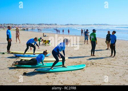 Peniche, PORTUGAL - 30 juillet 2017: la formation des étudiants de l'école de surf à la plage de Baleal bondé avec moniteur en journée ensoleillée, paysage marin en arrière-plan Banque D'Images
