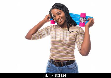 Jeune femme en jeans et chemise posant avec un sourire sincère sur fond bleu. Cute african girl holding skateboard et rire. Banque D'Images