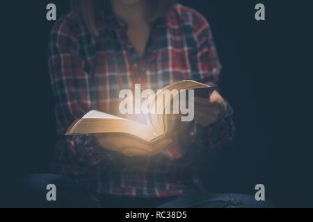 Jeune femme readin bible dans une pièce sombre