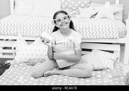 Concept d'anniversaire. Happy girl got cadeaux d'anniversaire. Petit enfant dans fantaisie lunettes sourire avec smartphone sur anniversaire. Joyeux anniversaire surprise. Banque D'Images