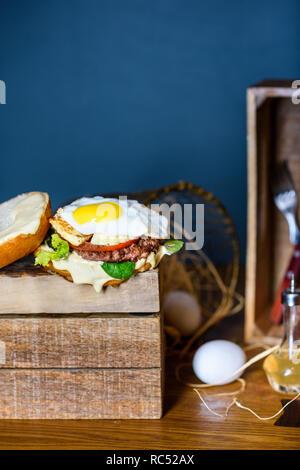 Burger de boeuf, l'oeuf et le fromage. Frites avec du romarin. Close up, copiez l'espace. Banque D'Images