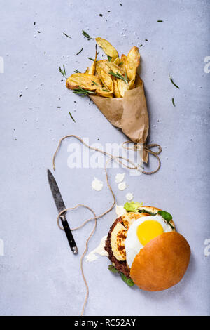 Burger classique avec le boeuf, l'oeuf et le fromage. Frites avec du romarin. Vue de dessus, copiez l'espace. Banque D'Images