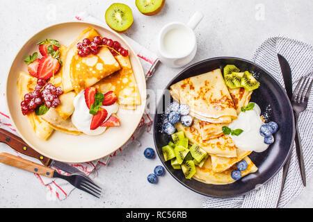Crêpes minces faits maison servis avec crème de fromage, fruits et baies en noir et blanc des plaques. Petit-déjeuner sain beau concept. Banque D'Images