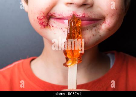 Garçon suce sucette, bébé mange rouge-orange-chupa chups, bouche, lèvres roses, des bonbons dans la main, la moitié de visage du garçon Banque D'Images