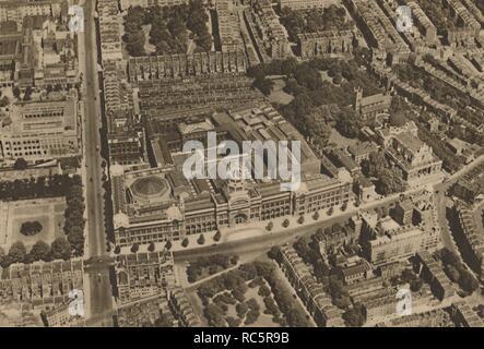 """'L'appareil photo prend un avis de South Kensington à partir d'un avion Low-Flying', c1935. Le V&un musée de South Kensington, dans le centre de Londres, a été fondée en 1852 et nommée d'après la reine Victoria et le Prince Albert. La zone a été établie par Albert dans le cadre de l'Exposition Universelle de 1851. Sur la gauche se trouve le Musée des sciences sur la route menant à l'exposition des jardins de Kensington, l'entrée principale du musée sur Cromwell Road peut être vu dans le centre, avec Brompton Oratory à droite. """"Magnifique de Londres, Volume 3"""", édité par Arthur St John Adcock. [Le Fleetway House, Londres, c1935] Banque D'Images"""