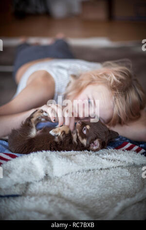 Teenage girl lying on floor et jouer avec puppy Banque D'Images