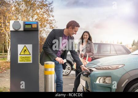 L'homme et la femme à la voiture électrique de charge charge voiture Park, Manchester, UK