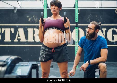 Directeurs formateur femme enceinte à l'aide de poids dans une salle de sport