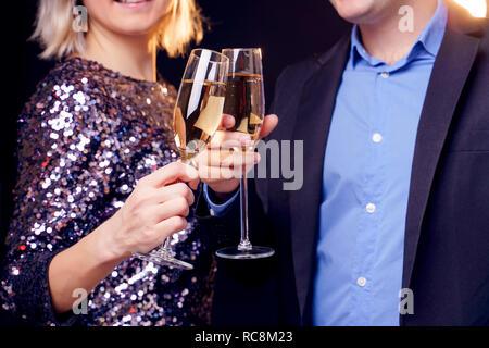 Photo de jeune couple avec verres de champagne en studio Banque D'Images