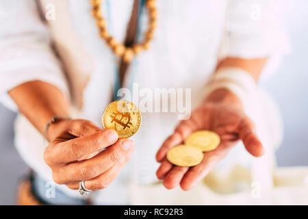 Femme d'âge moyen et l'utilisation des mains d'or pièce de monnaie bitcoin pour montrer de nouvelles technologie moderne argent virtuel cryptocurrency - concept commercial Commerce Business Daily Banque D'Images