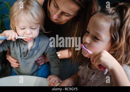 Mère d'aider les enfants à se brosser les dents Banque D'Images