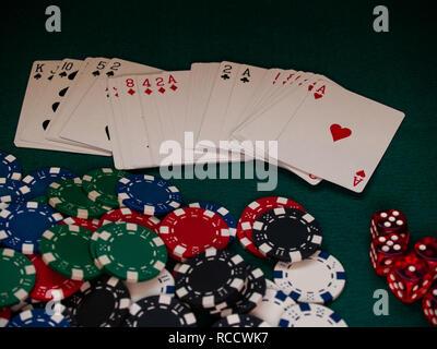 Un jeu de poker, des jetons de poker de différentes couleurs et plusieurs dés sur un tapis vert