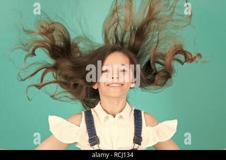 Sourire de fille avec des cheveux sur fond bleu. Sourire de l'enfant avec de longs cheveux sains. Salon de concept. Soins des cheveux, coiffure, coiffure, salon de coiffure, pastel punchy Banque D'Images
