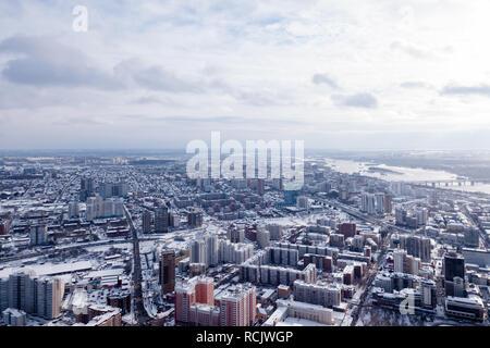 Paysage d'hiver à partir d'une vue aérienne de la ville de Novosibirsk dans la brume, de la rue avec une route, les grands bâtiments, maisons aux toitures sous white Banque D'Images