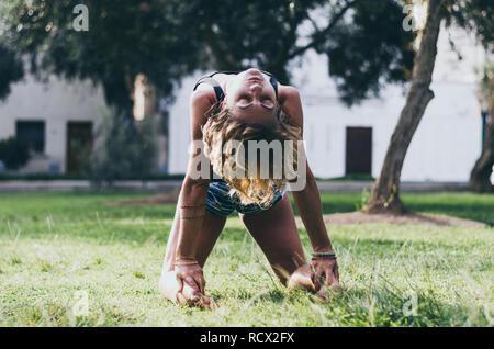 Yoga - plein air belle jeune femme svelte instructeur de yoga asana Ustrasana camel faire poser l'exercice à l'extérieur. Effet Retro Vintage style hipster filtré de l'image.