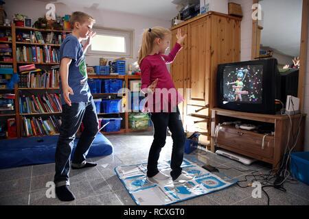 Frères et sœurs, un garçon, 12 ans, et une fille, 10 ans, de jouer à un jeu de danse sur Wii une console de jeux dans leur chambre ensemble Banque D'Images