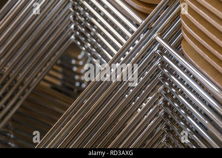 Chaises empilées avec sièges en bois et métalliques jambes Banque D'Images
