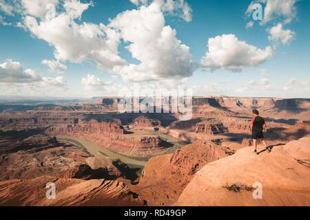 Un jeune randonneur est debout sur le bord d'une falaise offrant une vue sur le célèbre fleuve du Colorado, Dead Horse Point State Park. Dans l'Utah, aux Etats-Unis Banque D'Images