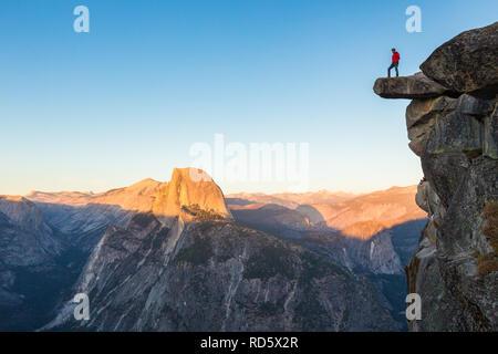 L'intrépide randonneur est debout sur un rocher en surplomb en profitant de la vue vers célèbre Demi Dôme à Glacier Point oublier dans beau crépuscule du soir Banque D'Images