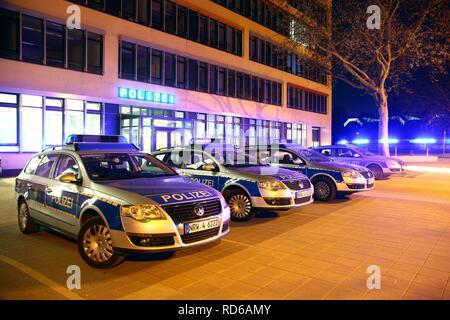 Voiture de police de prendre la route de feux clignotants, des voitures de patrouille garé en face d'une station de police moderne, Gelsenkirchen Banque D'Images