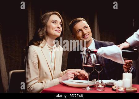 Waiter pouring red wine while smiling couple having date romantique au restaurant Banque D'Images