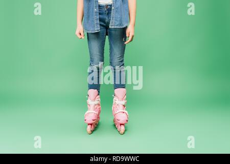 Portrait de l'enfant portant le denim, les rollers rose sur fond vert Banque D'Images