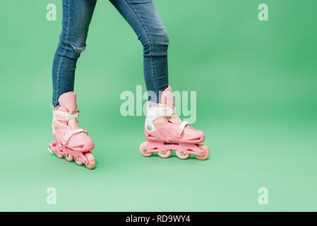 Vue partielle de l'enfant portant le jean et rose rollers isolé sur green Banque D'Images
