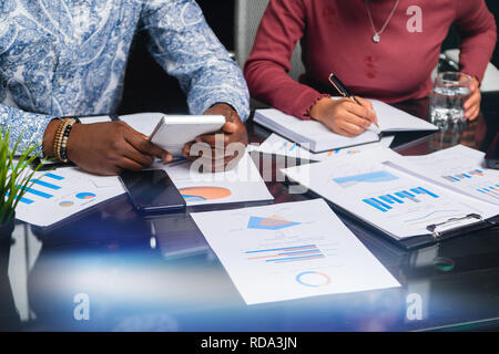 Mains de tenir les personnes à peau brune de la calculatrice financière documents dans l'espace libre d'affaires