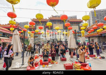 Les fidèles des la Sik Sik Yuen Wong Tai Sin Temple Hong Kong le culte de la lumière sur l'autel des bâtons avant de faire un choix. Banque D'Images