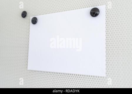 Feuille de papier blanc sur un tableau magnétique fixe avec deux aimants rond noir. Avec l'exemplaire de l'espace. Banque D'Images