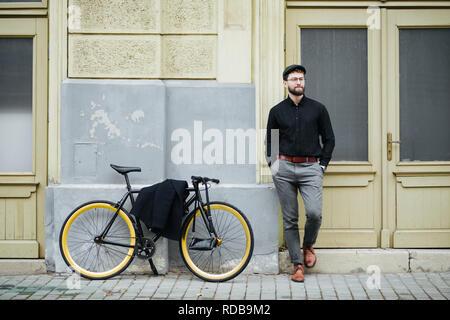 Portrait de beau jeune homme dans les tenues à l'écart et souriant tout en se penchant près de vélo, standing outdoors