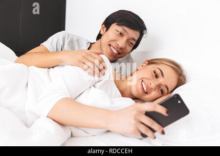 Belle jeune couple laying in bed, young girl using mobile phone Banque D'Images