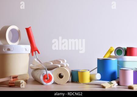 Outils de peinture pour mur à mur blanc avec table Banque D'Images