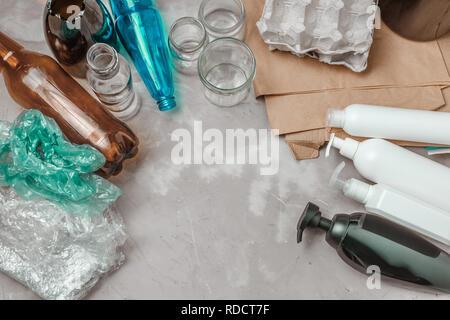 Différents types de déchets, le sac en plastique, papier froissé, les contenants en plastique, le verre et les bouteilles sur la table. Concept de gestion du tri des déchets Banque D'Images