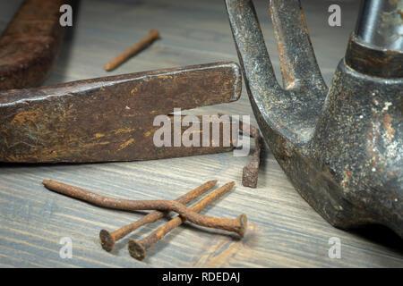 Vieux clous rouillés avec deux marteaux griffe dans un close up portrait dans un entretien, la réparation, la construction ou la notion de bricolage Banque D'Images