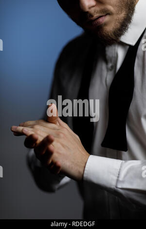Mains de jeune homme barbu en chemise et noeud papillon déliée Banque D'Images