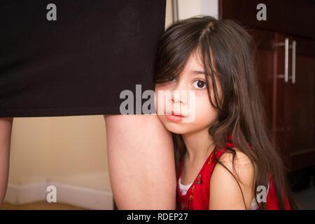 Petite fille tient la jambe de sa mère à la triste Banque D'Images