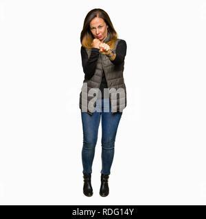 Belle femme d'âge moyen portant veste hiver prêt à combattre avec fist, geste de défense en colère et contrarié face, peur de problème Banque D'Images