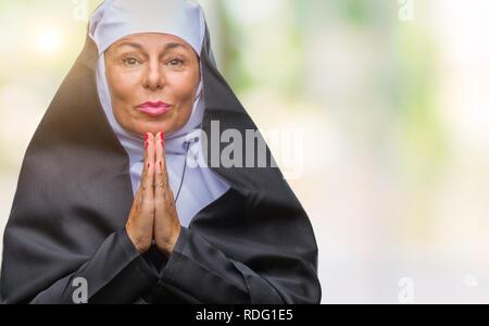 L'âge moyen des hauts femme religieuse catholique chrétienne sur fond isolé en prière avec les mains pour lui demander pardon sourire confiant. Banque D'Images