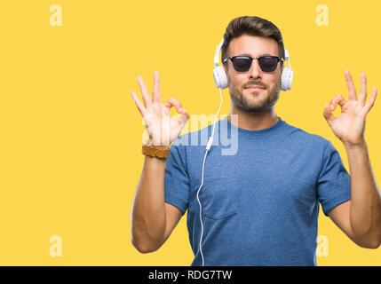 Young man wearing headphones listening to music sur fond isolé vous détendre et souriant avec les yeux fermé faisant geste de méditation avec fin Banque D'Images