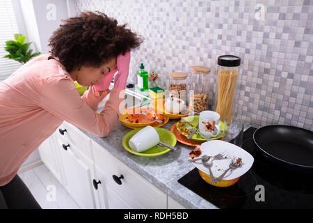 Assez jeune femme se penchant près de l'évier avec des ustensiles colorés sales dans la cuisine Banque D'Images